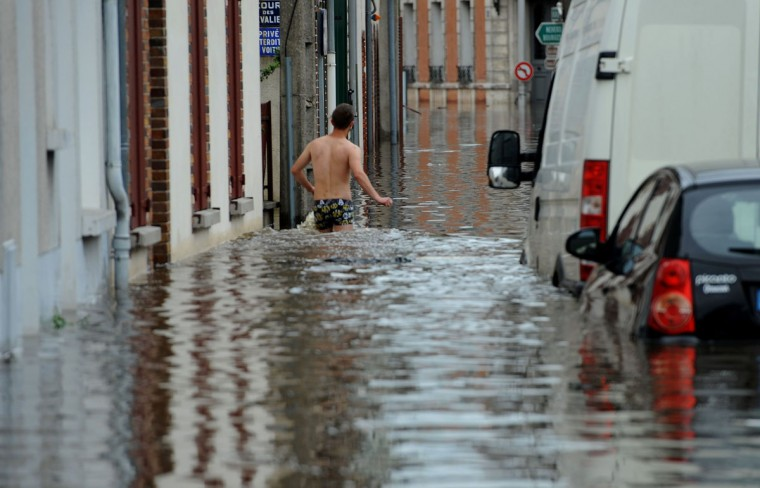 A man stands in the flooded street in underwear as the city is flooded due to heavy rainfalls at Montargis, central France, on June 01, 2016. Torrential downpours have lashed parts of northern Europe in recent days, leaving four dead in Germany, breaching the banks of the Seine in Paris and flooding rural roads and villages. (AFP PHOTO / GUILLAUME SOUVANT)