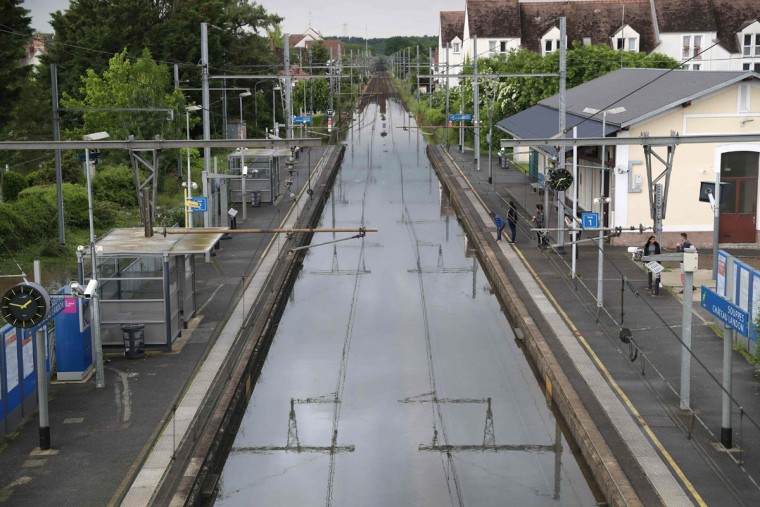People stand next to flooded railway tracks on June 1, 2016 in Souppes-sur-Loing, southeast of Paris. Torrential downpours have lashed parts of northern Europe in recent days, leaving four dead in Germany, breaching the banks of the Seine in Paris and flooding rural roads and villages. (AFP PHOTO / KENZO TRIBOUILLARD)