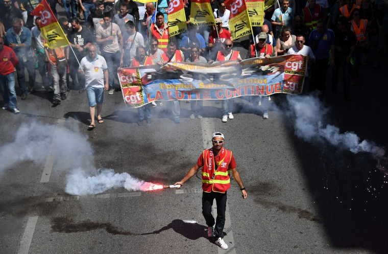 A man holds a smoke flare as people take part in a demonstration against the French government's planned labour law reforms, on June 2, 2016 in Marseille, southern France. France suffered a third day of rail strikes on June 2, 2016, but fears of transport chaos during the Euro 2016 football tournament eased as airport workers cancelled a walkout and a Paris subway strike had little impact. More demonstrations against the reforms -- which the government says are designed to make France more business-friendly -- took place in major cities on June 2 and workers were back on strike at 16 of the country's 19 nuclear power stations. (Anne-Christine Poujoulat/AFP/Getty Images)