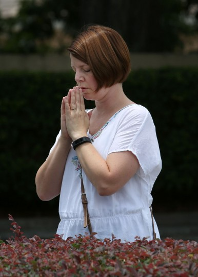 A woman prays at a site about a block from the Pulse nightclub in the aftermath of a mass shooting in Orlando, Florida, on June 12, 2016. Fifty people died and another 53 were injured when a gunman opened fire and seized hostages at the Pulse, a gay nightclub in Orlando, Florida, police said June 12, making it the worst mass shooting in US history. (AFP PHOTO / Gregg NEWTON)