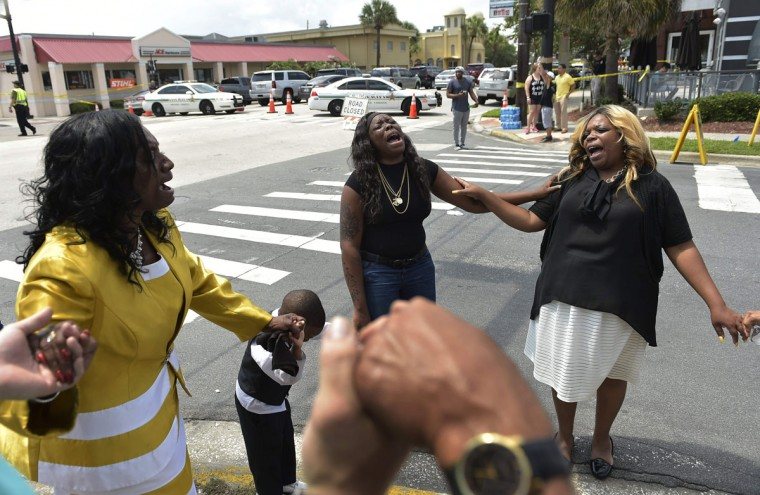 """Women pray near the area of the mass shooting at the Pulse nightclub on in Orlando, Florida on June 12, 2016. A somber President Barack Obama expressed grief and outrage at the """"horrific massacre"""" of 50 late-night revelers at an Orlando gay club, branding it an act of terror and hate. (AFP PHOTO / Mandel NGAN)"""
