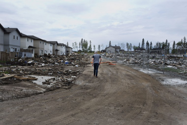 A Fort McMurray resident looks over the damage in the neighborhood of Timberlea in Fort McMurray, Canada, on Wednesday, June 1, 2016. Residents started to return to the fire-damaged city in northern Alberta on Wednesday, but officials have warned that they should not expect everything to be running normally right away. (Jason Franson/The Canadian Press via AP)