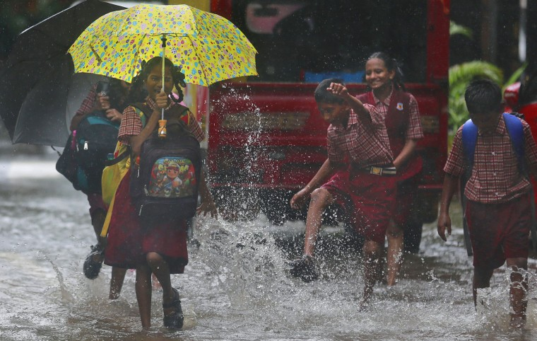 A schoolgirl reacts to rainwater being splashed on her, in a flooded street in Mumbai, India, Tuesday, June 28, 2016. Monsoon rains, which started off slow in the city, has picked up pace the past few days. India's monsoon season runs from June to September. (AP Photo/Rafiq Maqbool)