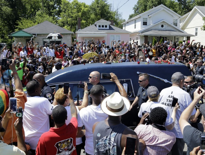 The hearse carrying the body of Muhammad Ali passes in front of his boyhood home, top center, during his funeral procession Friday, June 10, 2016, in Louisville, Ky. (AP Photo/Mark Humphrey)