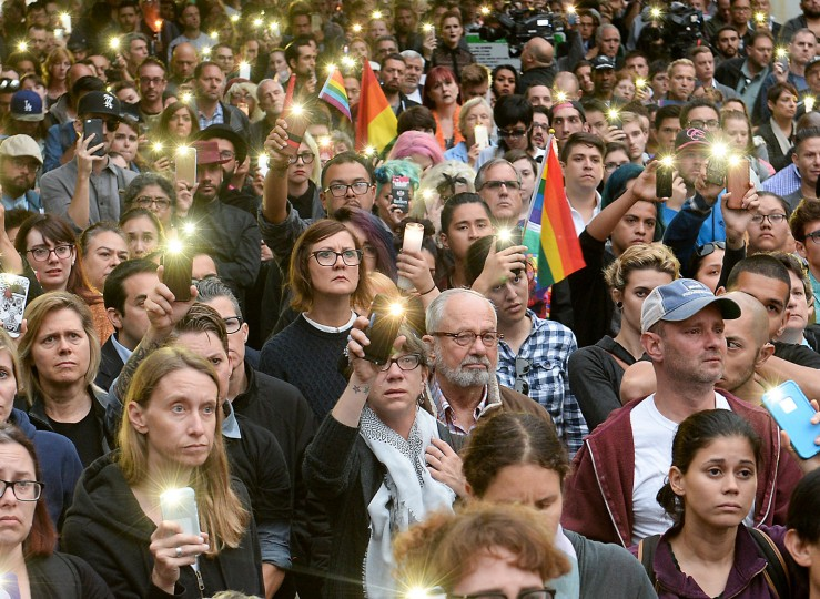 Supporters light candles and shine their mobile phone lights during the Los Angeles Rally and Vigil for Orlando at Los Angeles City Hall in Los Angeles, on Monday June 13, 2016. Vigils, rallies and marches are being held around the country Monday for the victims of the deadly attack at a gay nightclub Sunday in Orlando, Fla., the worst mass shooting in modern U.S. history. (Keith Durflinger/Los Angeles Daily News via AP)