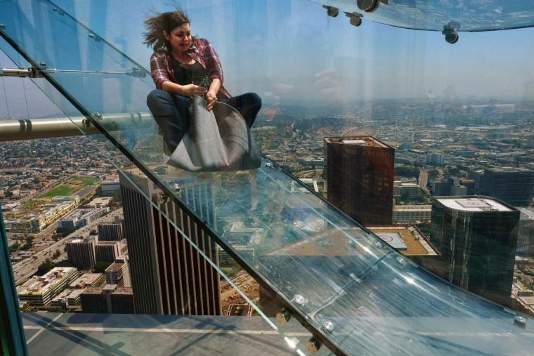 A member of the media rides down a glass slide during a media preview at the U.S. Bank Tower building in downtown Los Angeles on Thursday, June 23, 2016. Starting this weekend, thrill-seekers can begin taking the Skyslide, a 1,000 feet high slide, perched on the outside of the tallest skyscraper west of the Mississippi. (AP Photo/Richard Vogel)