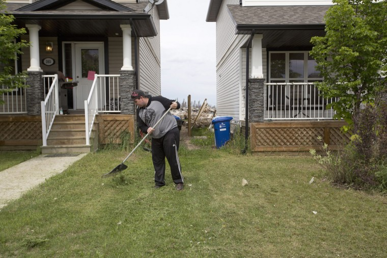 Resident Kenny Gibbons rakes his lawn in the neighborhood of Timberlea, in Fort McMurray Alberta, on Wednesday, June 1, 2016. Residents began returning to their homes after being evacuated due to wildfires. People returning Wednesday lived in areas that were mostly spared by the flames. Residents in harder hit areas are to return in the coming days. (Jason Franson/The Canadian Press via AP)