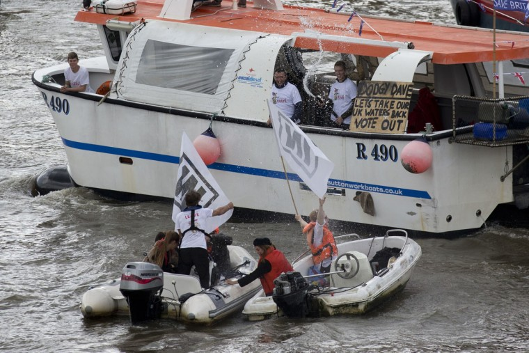 "In an EU referendum campaign stunt, men on a boat wearing ""leave"" t-shirts spray water from a hose at people holding ""In"" banners, one of whom also appears to be wearing a ""leave"" t-shirt of the same design as the leave supporters on the River Thames outside the Houses of Parliament in London, Wednesday, June 15, 2016. A flotilla of boats protesting EU fishing polices has sailed up the River Thames to the Houses of Parliament as part of a campaign backing Britain's exit from the European Union. The flotilla was greeted by boats carrying ""remain"" supporters. (AP Photo/Matt Dunham)"