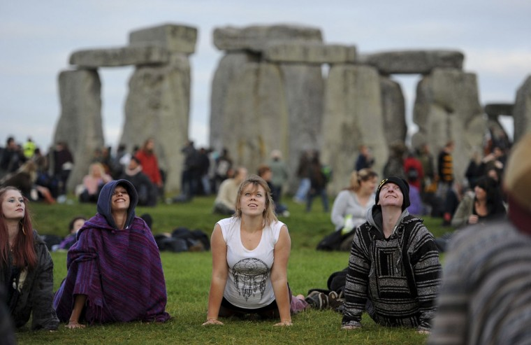 People perform yoga as they gather at the ancient stone circle Stonehenge, during the Summer Solstice, the longest day of the year, in Wiltshire Tuesday June 21, 2016. (Andrew Matthews/PA via AP)