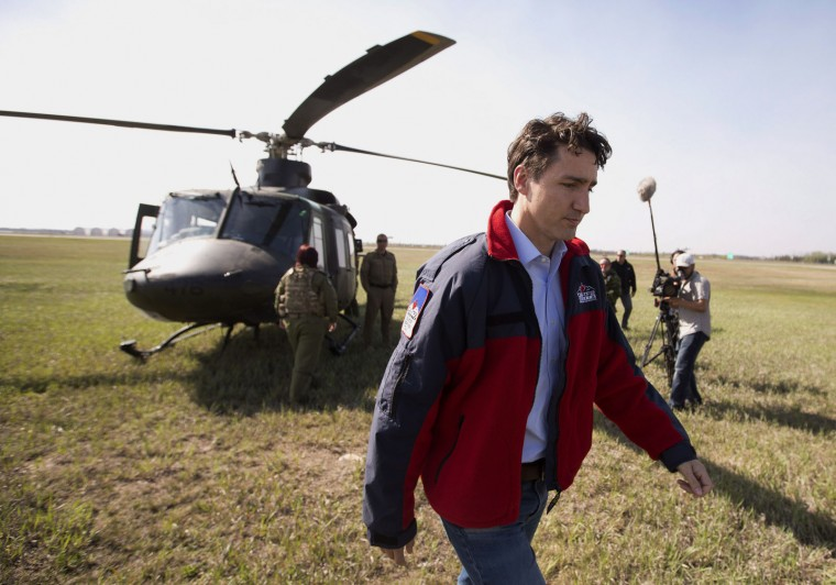 Prime Minister Justin Trudeau leaves the helicopter during a visit to see the devastation caused by the wildfire, in Fort McMurray, Canada., Friday, May 13, 2016. (Jason Franson/The Canadian Press via AP)