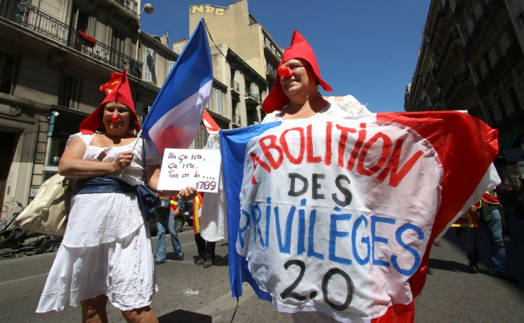 "Protestors wearing Phrygian caps and holding French national flags reading ""Abolition of privileges"", demonstrate in Marseille, southern France, Thursday, June 2, 2016. Several thousand protestors are demonstrating during a day of strikes and protest against the law job government reform. (AP Photo/Claude Paris)"