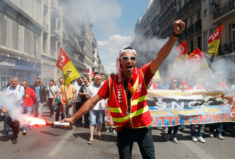 A railway worker burns a flare and shouts slogans during a demonstration in Marseille, southern France, Thursday, June 2, 2016. Several thousands of protestors demonstrate during a day of strikes and protest against the law job government reform. (AP Photo/Claude Paris)