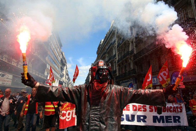 A steelworker from the ArcelorMittal steel plant in Fos-sur-Mer wearing a mask of Darth Vader burns flares during a demonstration in Marseille, southern France, Thursday, June 2, 2016. Several thousand protestors are demonstrating during a day of strikes and protest against the law job government reform. (AP Photo/Claude Paris)