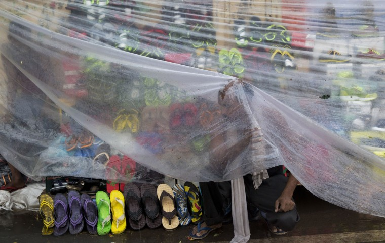 A roadside vendor selling cheap footwear takes cover under a plastic sheet as it rains in Allahabad, India, Thursday, June 23, 2016. After a couple of years of deficient monsoons, the Indian meteorological department has predicted a wetter than normal monsoon season in 2016. (AP Photo/ Rajesh Kumar Singh)