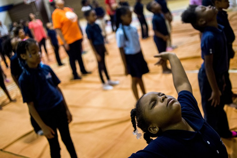 Second-grader Da'naya Jones stretches her arms out as she practices neck exercises with other students - grades 2 through 8 - learn and practice yoga in a school-wide initiative on International Yoga Day on Tuesday, June 21, 2016 at The New Standard tuition-free charter school, in Flint, Mich. (Jake May/The Flint Journal-MLive.com via AP)