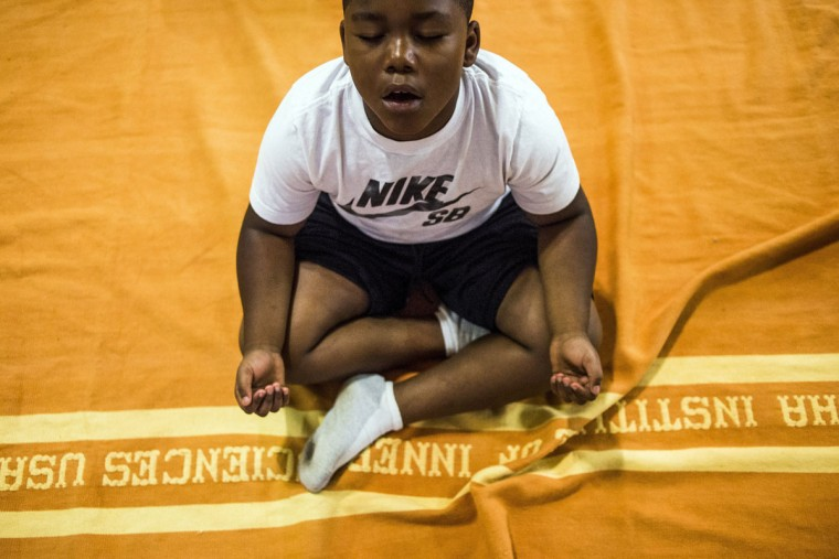 Second-grader Ramon Pope practices nada yoga using sounds and tones to create inner transformations while exhaling out with a long moaning sound as students - grades 2 through 8 - learn and practice yoga in a school-wide initiative on International Yoga Day on Tuesday, June 21, 2016, at The New Standard tuition-free charter school, in Flint, Mich. (Jake May/The Flint Journal-MLive.com via AP)