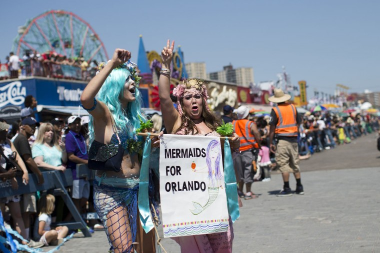 "Participants hold a ""Mermaids for Orlando"" sign as they march on the boardwalk during the 34th Annual Mermaid Parade, Saturday, June 18, 2016, in New York's Coney Island. (AP Photo/Mary Altaffer)"