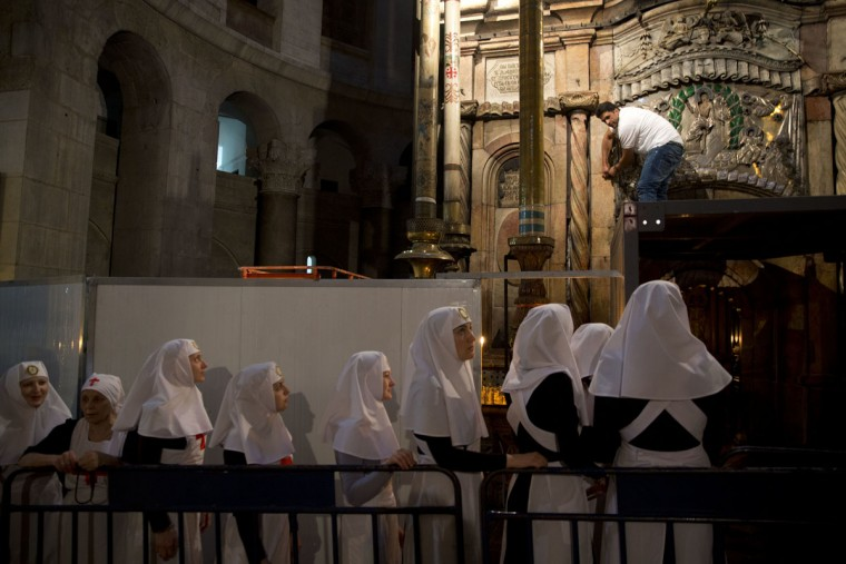 Christian nuns watch as a team of experts begin renovation of Jesus' tomb in the Church of the Holy Sepulchre in Jerusalem's old city, Monday, June 6, 2016. A team of experts has begun a historic renovation at the spot where Christians believe Jesus was buried, overcoming longstanding religious rivalries to carry out the first repairs at the site in over 200 years. (AP Photo/Ariel Schalit)