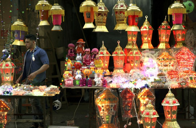 A Palestinian vendor stands between lighted traditional Ramadan lanterns while waiting for customers at the main market in Gaza City, Friday, June 3, 2016. Devout Muslims throughout the world will begin to celebrate Ramadan next week, the holiest month in the Islamic calendar, refraining from eating, drinking, smoking and sex from sunrise to sunset. (AP Photo/Adel Hana)