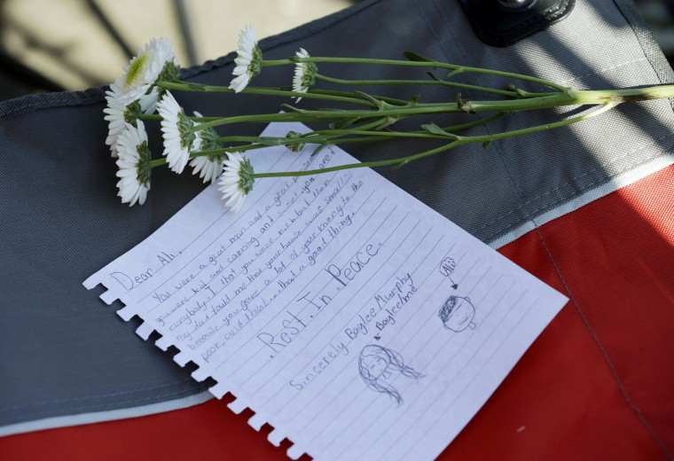 A letter of tribute and flowers sit on a chair as fans await the funeral procession for Muhammad Ali to make its way down Muhammad Ali Boulevard in Louisville, Ky. Friday, June 10, 2016. (AP Photo/Michael Conroy)