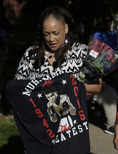 Robin Marshall holds a t-shirt and flowers as she waits for the procession to pass with the hearse carrying the body of Muhammad Ali, Friday, June 10, 2016, in Louisville, Ky. (AP Photo/Darron Cummings)