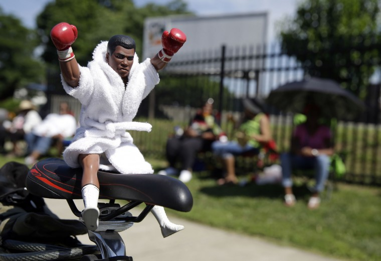 A Muhammad Ali action figure sits on the seat of a bicycle as fans await the funeral procession for the late boxing champion to make its way down Muhammad Ali Boulevard in Louisville, Ky. Friday, June 10, 2016. (AP Photo/Michael Conroy)