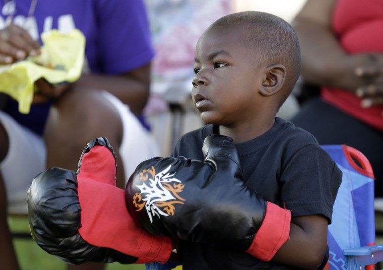 Tymetrius Steward, 3, wears boxing gloves to honor Muhammad Ali as he awaits his funeral procession to make its way down Muhammad Ali Boulevard in Louisville, Ky. Friday, June 10, 2016. (AP Photo/Michael Conroy)