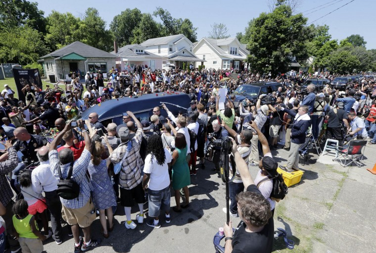 The hearse carrying the body of Muhammad Ali passes in front of his boyhood home during his funeral procession Friday, June 10, 2016, in Louisville, Ky. Ali's home is the second house from the left. (AP Photo/Mark Humphrey)
