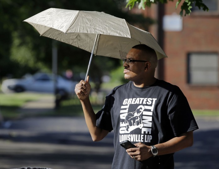 Dale James waits for the procession to pass with the hearse carrying the body of Muhammad Ali, Friday, June 10, 2016, in Louisville, Ky. (AP Photo/Darron Cummings)