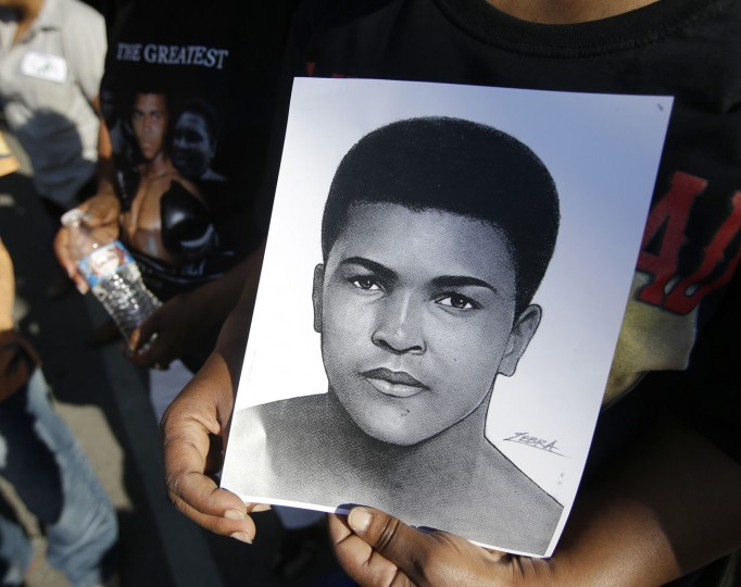 A mourner holds a photo of Muhammad Ali, as she waits for the procession to pass with the hearse carrying the body of Muhammad Ali, Friday, June 10, 2016, in Louisville, Ky. (AP Photo/Darron Cummings)