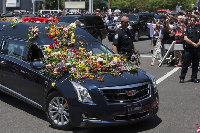 Flowers pile up on the hearse carrying Muhammad Ali spectators watch his funeral procession enter Cave Hill Cemetery, Friday, June 10, 2016, in Louisville, Ky. (AP Photo/John Minchillo)