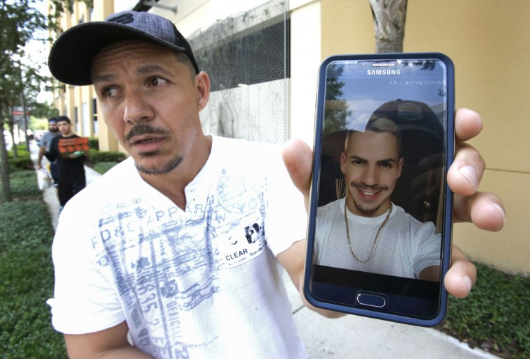 Angel Mendez, standing outside the Orlando Regional Medical Center, holds up a cell phone photo trying to get information about his brother Jean C. Mendez that was at the Pulse Nightclub where a shooting involving multiple fatalities occurred, Sunday, June 12, 2016, in Orlando, Fla. (AP Photo/John Raoux)