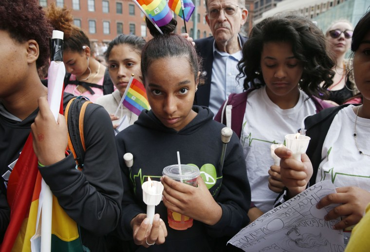Alianna Arias, center, of Boston, holds a candle during a vigil on City Hall Plaza for the victims in the Orlando nightclub attack, Monday, June 13, 2016, in Boston. (AP Photo/Michael Dwyer)