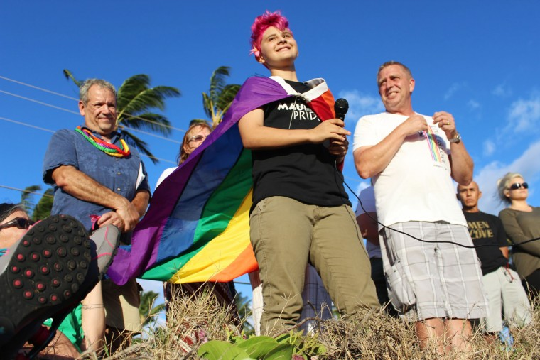 In this Monday, June 13, 2016 photo, Jaysen Giroux, center, concludes a poem written for the Orlando, Fla., nightclub victims in Kihei, Hawaii. Speakers encouraged the crowd to not give in to fear and to help educate others on actions or language that may hurt the LGBT community. (Colleen Uechi/The News via AP)