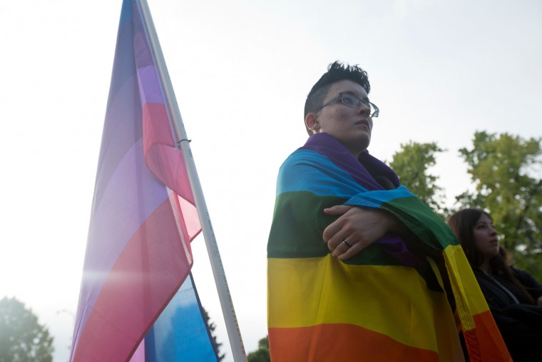 Draped in a pride flag, an attendee listens during a vigil for the Orlando shooting victims at Memorial Park in Provo, Monday, June 13, 2016. Over 200 people attended the event which featured speakers from local groups like PFLAG and Resilient Hope. (Sammy Jo Hester/The Daily Herald via AP)