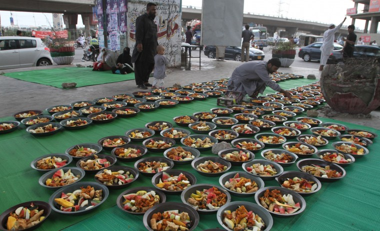 Pakistani volunteers arrange food for people to break their fast at dusk in Karachi, Pakistan, Friday, June 17, 2016. Muslims across the world are observing the holy fasting month of Ramadan, when they refrain from eating, drinking and smoking from dawn to dusk. (AP Photo/Fareed Khan)