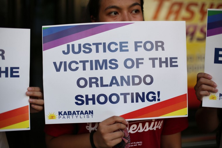 A Filipino youth activist holds a slogan as they gather in solidarity with victims of the mass shooting at the Pulse nightclub in Orlando, Florida during a gathering in Manila, Philippines on Tuesday June 14, 2016. The group calls for justice for the victims of the mass shooting. (AP Photo/Aaron Favila)