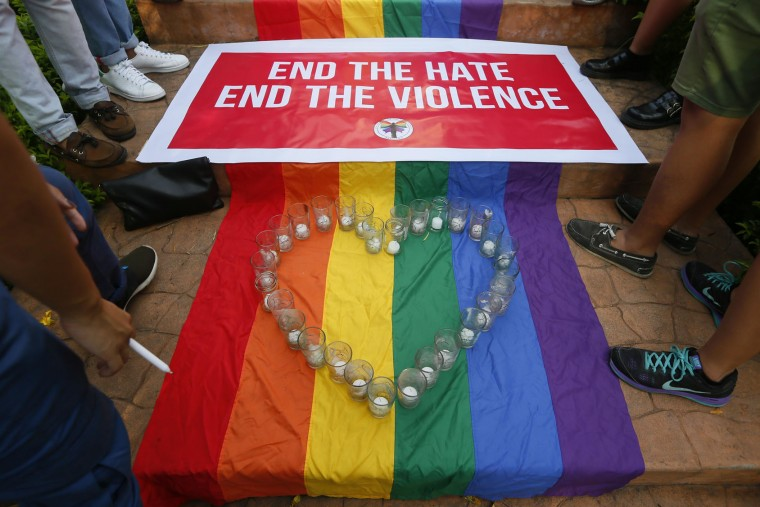 Filipino members of the LGBT (Lesbian, Gay, Bisexual, Transgender) community stand around a rainbow flag with a heart-shaped symbol during a vigil to pay tribute to the victims of the Orlando, Fla. mass shooting Tuesday, June 14, 2016 at the University of the Philippines campus in suburban Quezon city northeast of Manila, Philippines. A gunman, later identified as Omar Mateen, opened fire inside a crowded gay nightclub early Sunday before dying in a gunfight with responding SWAT officers, authorities said. (AP Photo/Bullit Marquez)