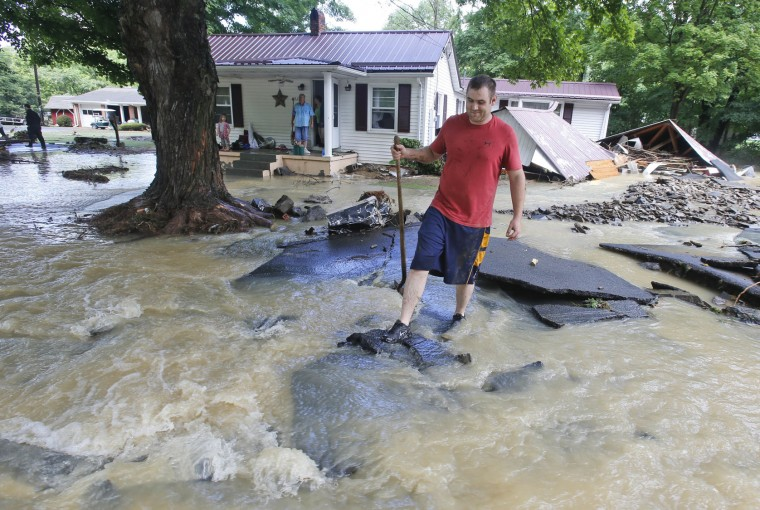 Mark Bowes, of White Sulphur Springs W. Va., makes his way to the road as he cleans up from severe flooding in White Sulphur Springs, W. Va., Friday, June 24, 2016. A deluge of 9 inches of rain on parts of West Virginia destroyed or damaged more than 100 homes and knocked out power to tens of thousands of homes and businesses. (AP Photo/Steve Helber)