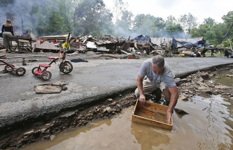 Mark Lester cleans out a box with creek water as he cleans up from severe flooding in White Sulphur Springs, W. Va., Friday, June 24, 2016. A deluge of 9 inches of rain on parts of West Virginia destroyed or damaged more than 100 homes and knocked out power to tens of thousands of homes and businesses. (AP Photo/Steve Helber)