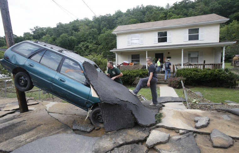 Jay Bennett, left, and step-son Easton Phillips survey the damage to a neighbors car in front of their home damaged by floodwaters as the cleanup begins from severe flooding in White Sulphur Springs, W. Va., Friday, June 24, 2016. A deluge of 9 inches of rain on parts of West Virginia destroyed or damaged more than 100 homes and knocked out power to tens of thousands of homes and businesses. (AP Photo/Steve Helber)