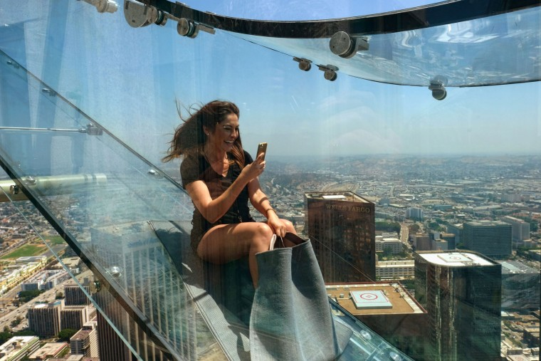 "Angela Cox, a reporter with Seven Network Australia, takes a photo with her phone as she takes ride down a glass slide during a media preview day at the U.S. Bank Tower building in downtown Los Angeles on Thursday, June 23, 2016. Starting this weekend, thrill-seekers can begin taking the ""Skyslide"" a 1,000 feet high and perched on the outside of the tallest skyscraper west of the Mississippi. All that separates riders from the dizzying space below is a piece of glass just 1 1/4 inches thick. (AP Photo/Richard Vogel)"