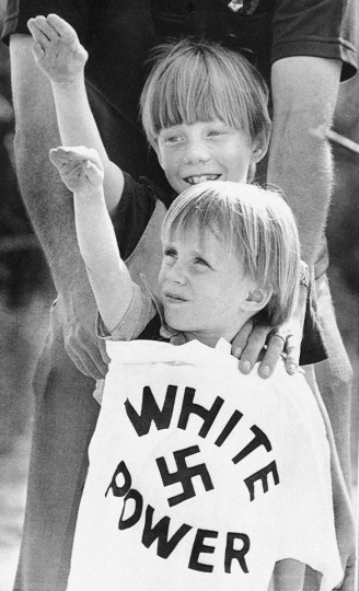 In this April 20, 1980 file photo, two young boys raise their arms as a white power T-shirt is held in front of them during a Klan rally held near Benson, N.C. 150 years after it was founded, the Ku Klux Klan is trying to raise its hooded head, and the group dreams of again becoming an invisible empire spreading its tentacles throughout society. (AP Photo/Bob Jordan, File)
