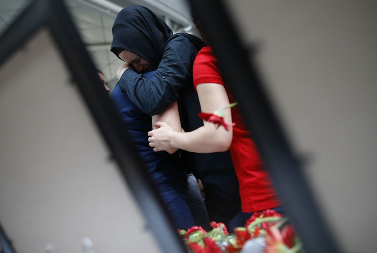 Two women embrace as family members, colleagues and friends of the victims of Tuesday blasts gather for a memorial ceremony at the Ataturk Airport in Istanbul, Thursday, June 30, 2016. A senior Turkish official on Thursday identified the Istanbul airport attackers as a Russian, Uzbek and Kyrgyz national hours after police carried out sweeping raids across the city looking for Islamic State suspects. Tuesday's gunfire and suicide bombing attack at Ataturk Airport killed dozens and injured over 200. Turkish authorities have banned distribution of images relating to the Ataturk airport attack within Turkey. (AP Photo/Emrah Gurel)