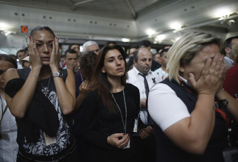 People react as family members, colleagues and friends of the victims of Tuesday blasts gather for a memorial ceremony at the Ataturk Airport in Istanbul, Thursday, June 30, 2016. A senior Turkish official on Thursday identified the Istanbul airport attackers as a Russian, Uzbek and Kyrgyz national hours after police carried out sweeping raids across the city looking for Islamic State suspects. Tuesday's gunfire and suicide bombing attack at Ataturk Airport killed dozens and injured over 200. Turkish authorities have banned distribution of images relating to the Ataturk airport attack within Turkey. (AP Photo/Emrah Gurel)