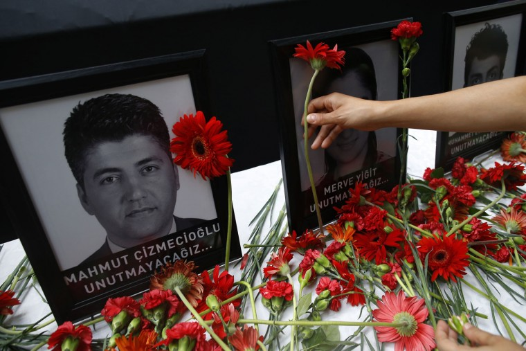 Photographs of victims displayed among carnations as family members, colleagues and friends gather for a memorial ceremony at the Ataturk Airport in Istanbul, Thursday, June 30, 2016. A senior Turkish official on Thursday identified the Istanbul airport attackers as a Russian, Uzbek and Kyrgyz national hours after police carried out sweeping raids across the city looking for Islamic State suspects. Tuesday's gunfire and suicide bombing attack at Ataturk Airport killed dozens and injured over 200. Turkish authorities have banned distribution of images relating to the Ataturk airport attack within Turkey. (AP Photo/Emrah Gurel)