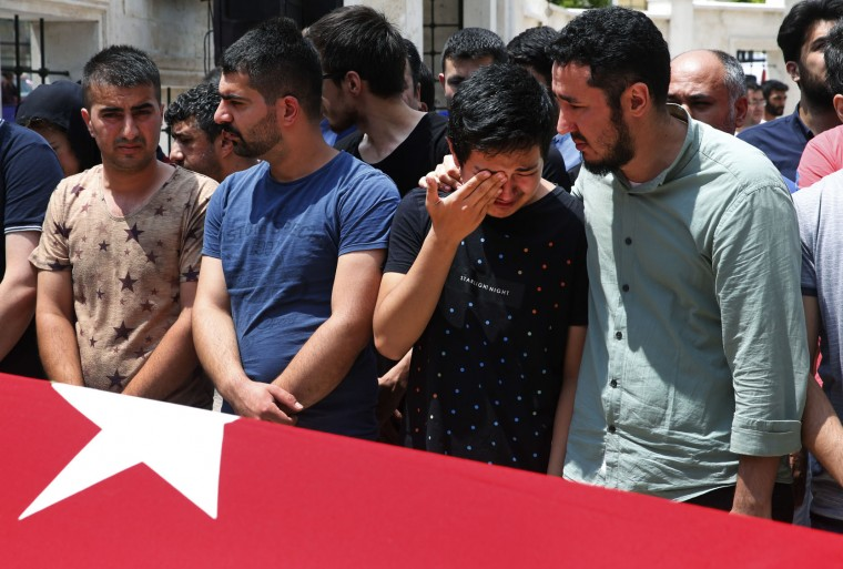 Relatives gather around the Turkish flag-draped coffin of Habibullah Sefer, one of the victims killed Tuesday at the blasts in Istanbul's Ataturk airport, during the funeral in Istanbul, Thursday, June 30, 2016. Suicide attackers killed dozens and wounded scores of others at the busy airport late Tuesday, the latest in a series of bombings to strike Turkey in recent months. Turkish authorities have banned distribution of images relating to the Ataturk airport attack within Turkey. (AP Photo/Lefteris Pitarakis)