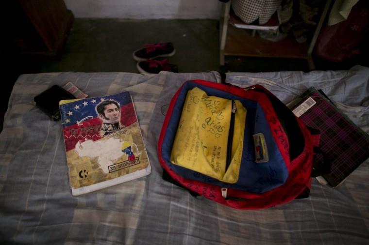 In this June 1, 2016 photo, Maria Arias' backpack and a book featuring Venezuela's independence hero Simon Bolivar sit on her bed before she leaves for school in Caracas, Venezuela. Arias' mother knows her children's grades have fallen this year, but isn't sure how much, because the school has not had supplies to print up report cards. (AP Photo/Ariana Cubillos)