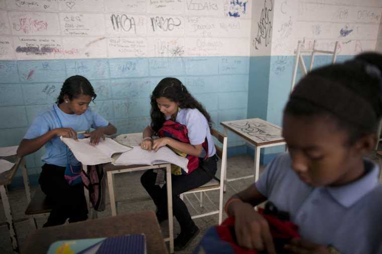 In this June 1, 2016 photo, Maria Arias, center, works with classmates during a math class at her public high school in Caracas, Venezuela. Arias has been held at gunpoint once in school, by a boy so baby-faced she assumed he was a classmate of her 15-year-old sister. Instead, he leveled a gun at her sister's ribs and demanded the girls' flip phones. (AP Photo/Ariana Cubillos)