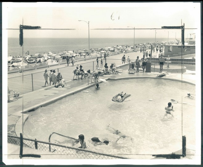 This is a typical summer scene at Rehoboth Beach, with vacationers enjoying the pool, strolling on boardwalk, just lolling on the beach, or frolicking in the ocean. Photo dated May 17, 1964.